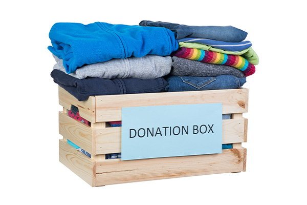Box labeled donation box with folded clothes inside.